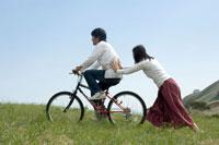 草原で自転車に乗った男性の背中を押す女性