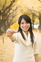 イチョウの葉を手に持つ若い女性