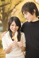 イチョウの葉を手に持つ若い女性と男性