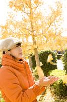 銀杏の落ち葉を手にする女性