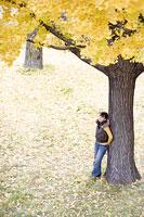 木によりかかる女性 11014007803| 写真素材・ストックフォト・画像・イラスト素材|アマナイメージズ