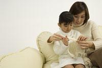 娘に編み物を教える母
