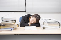 書類に埋もれ居眠りをする女性