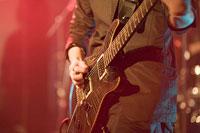 ステージでエレキギターを弾く男性