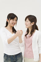 手を組む2人の女性
