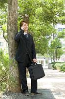 木の下で携帯電話で話す男性