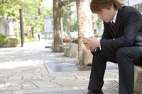 ベンチで携帯電話を眺める男性 11014019375| 写真素材・ストックフォト・画像・イラスト素材|アマナイメージズ