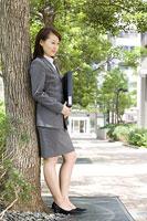 木に寄りかかって立つ女性 11014019376| 写真素材・ストックフォト・画像・イラスト素材|アマナイメージズ
