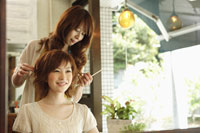 髪の長さを確認する美容師と女性
