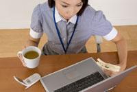 パソコンを見ながらサンドイッチを食べる女性