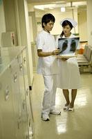廊下でレントゲンを見る看護師