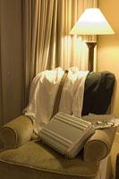 ホテル室内のソファの上のワイシャツとスーツケース