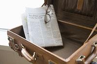 スーツケースの中の英字新聞と眼鏡