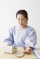 血圧を測る中年女性