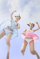 海岸でジャンプする水着の女性二人
