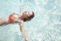 プールで水に浮かぶ水着の女性