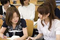 ノートを見ながら会話する女性2人