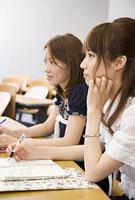 ノートを広げて講義を聞く女性2人