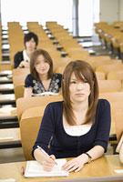 教室で講義を聞く女性2人と男性1人