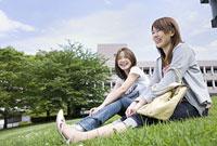 芝生に座る女性2人