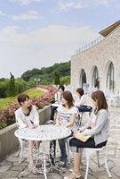 屋外テーブルで談笑する女性3人