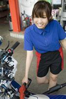 ガソリンスタンドで給油する女性店員