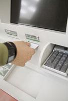 ATMにカードを入れる男性の手元