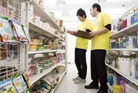 男性店員に商品陳列を指導するコンビニ店長 11014024032| 写真素材・ストックフォト・画像・イラスト素材|アマナイメージズ