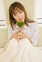 パジャマ姿でベッドの上に座り植物を持つ女性