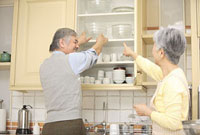 食器棚から食器を出そうとするシニアカップル