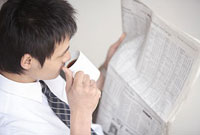 新聞を読みながらコーヒーを飲む男性