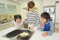 ベーコンエッグを作る母親と子供2人