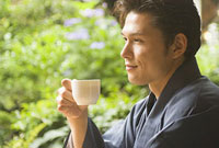コーヒーを飲む和服姿の男性