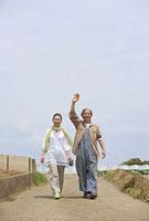 畑の中の道を歩くシニアカップル