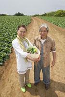 野菜かごを持って立つシニアカップル