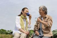 土手でコーヒーを飲むシニアカップル