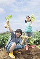 畑で収穫した野菜を持つ兄と妹