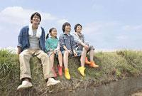 土手に座る親子4人