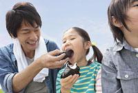 土手でおにぎりを食べる父と子供2人
