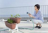 ベランダで植物に水を遣る女性