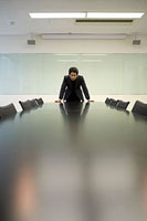 テーブルに手をついて正面を向く男性