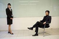 椅子に座る男性と向かいに立つ女性