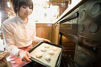 オーブンにパンを入れる女性