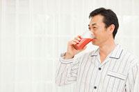 野菜ジュースを飲む中年男性