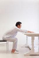五十肩体操をする中年男性