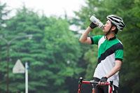 水を飲むサイクリングウェアの若い男性