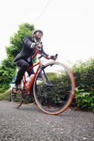 スーツ姿で自転車に乗る若い男性