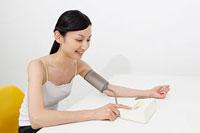 血圧を測る若い女性