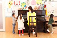ピアノで遊ぶ子供3人と保育士 11014028231| 写真素材・ストックフォト・画像・イラスト素材|アマナイメージズ