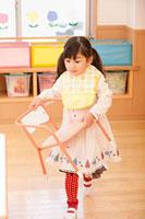 椅子を持って歩く女の子 11014028263| 写真素材・ストックフォト・画像・イラスト素材|アマナイメージズ
